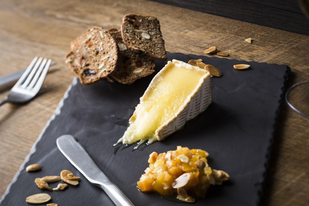 Tranche de fromage Riopelle servie coulante, confit d'abricots secs au citron